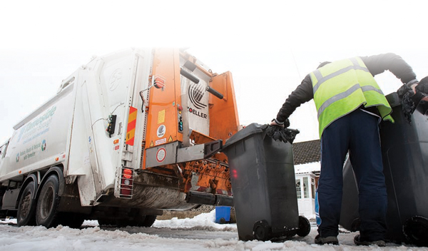 Refuse men collecting bins in the snow