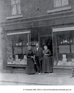 Old image of a family stood in front of a shop