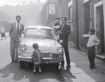 Old image of a family stood by a car