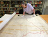 Researcher studying map in Tameside Local Studies and Archives