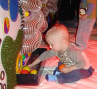 Photograph of a young child playing with sensory equipment