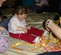 Photograph of a young child playing with fibre optic wires